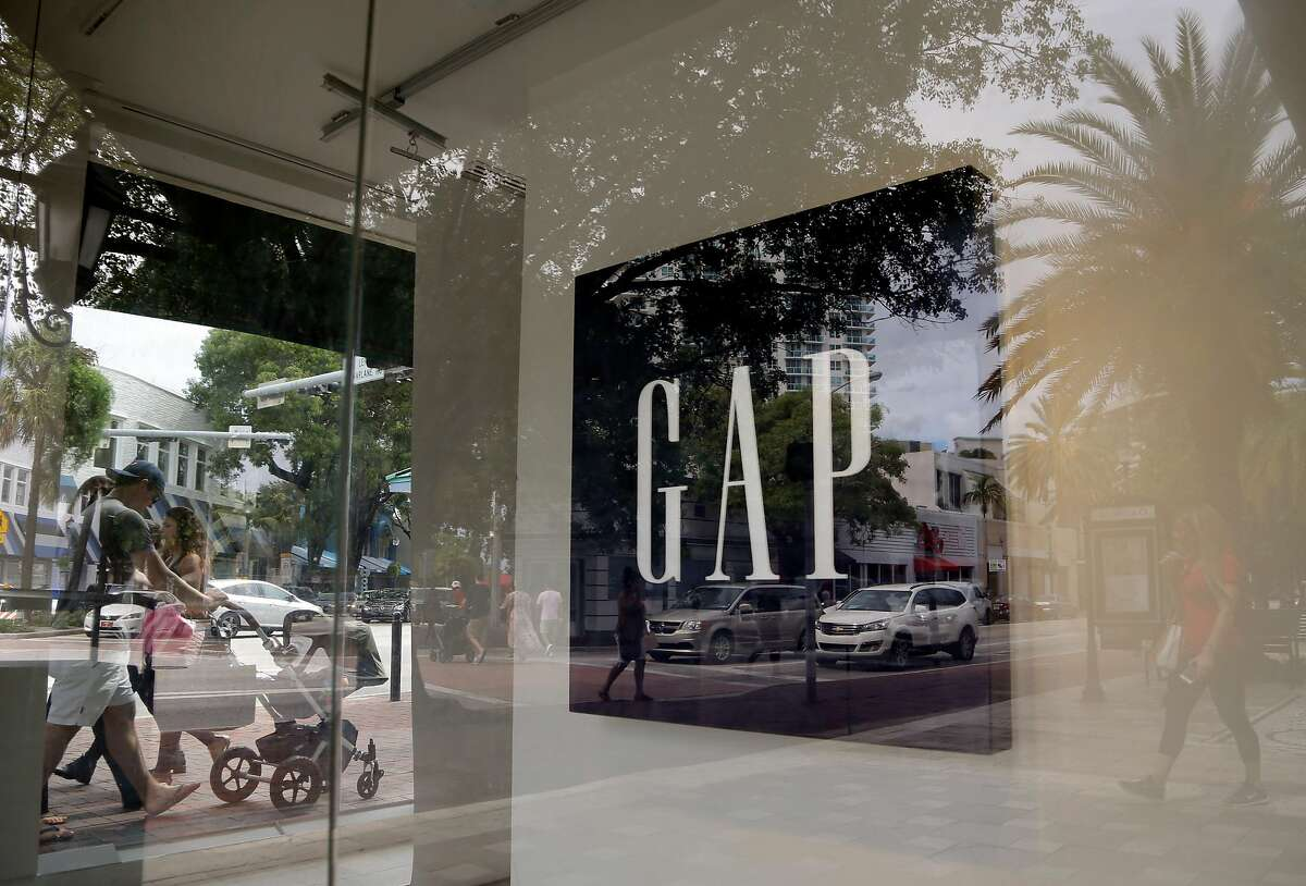 Pedestrians walks past a Gap store in Miami in 2015. Although Gap has closed most San Francisco stores, it is hiring for some holiday positions.