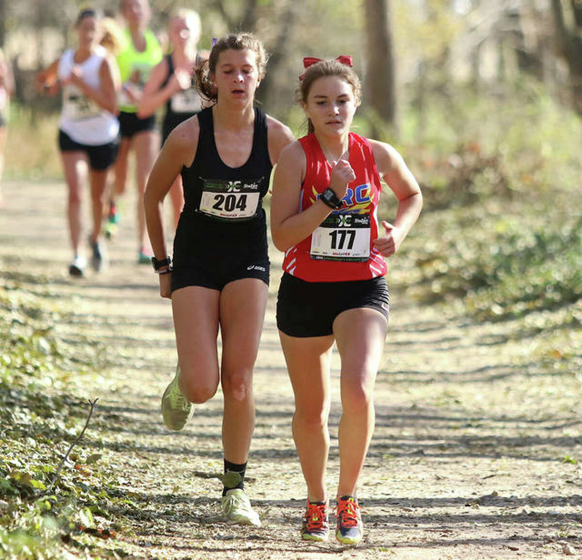 Roxana's Keiko Palen (front) leads runners through the woods at Three Sisters Park during Friday's ShaZam Racing 2020 High School XC Championships in Chillicothe. The Shells, running under the Roxana Running Club affiliation in the meet non-sanctioned by the IHSA, placed 10 in the Class 1A girls division.