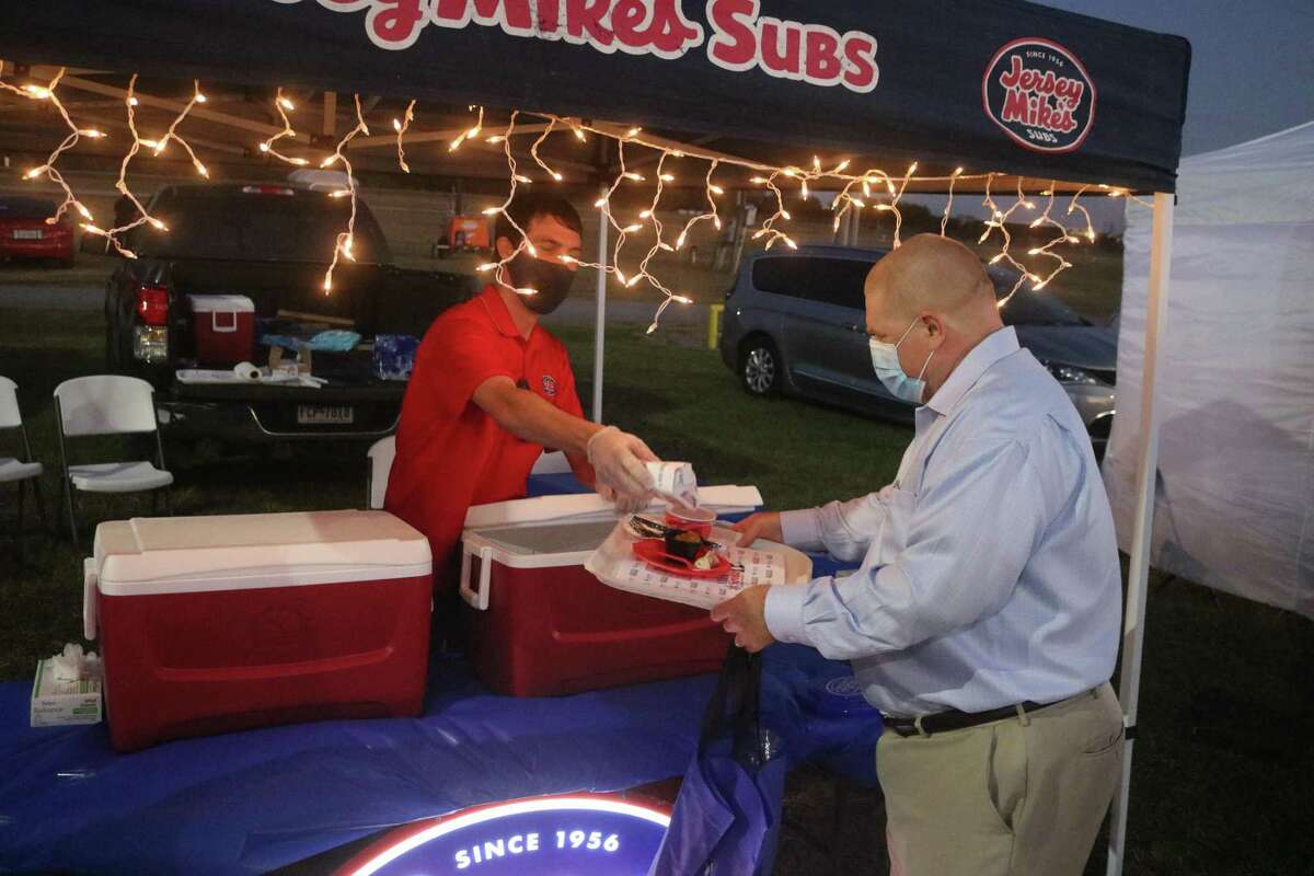 Matt Patrick helps a customer to a mini sub at the Jersey Mike's tent.