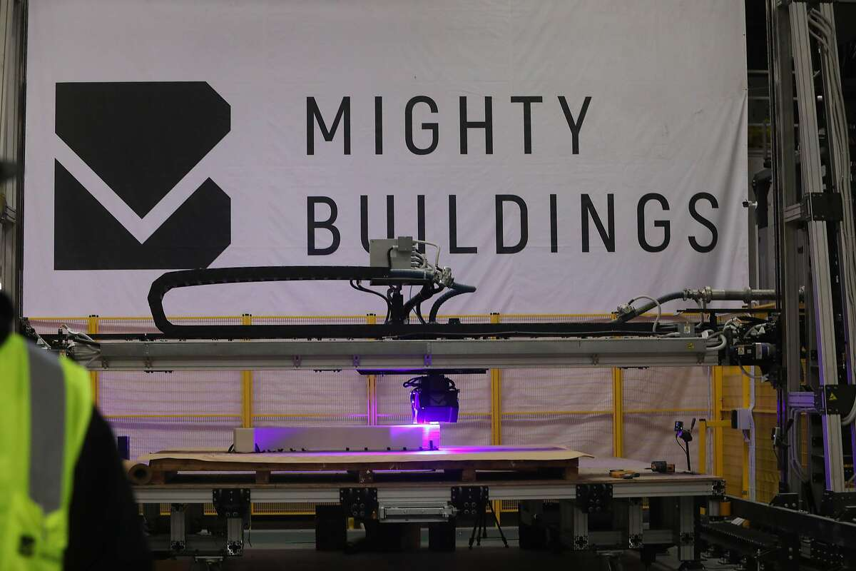 A 3-D printer is seen printing below a Mighty Buildings sign on Friday, November 6, 2020 in Oakland, Calif.