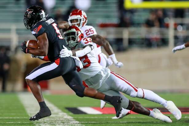 Defensive end Marcus Stripling #33 of the Oklahoma Sooners tackles running back Chadarius Townsend #5 of the Texas Tech Red Raiders during the second half of the college football game at Jones AT&T Stadium on October 31, 2020 in Lubbock. (Photo by John E. Moore III/Getty Images)