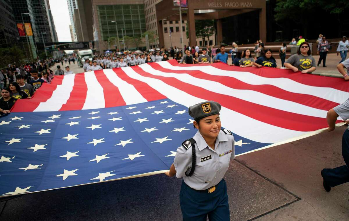 Members of the Milby High School JROTC march up Louisiana Street with a giant American Flag during the Houston Salutes American Heroes Veterans Day parade in downtown Houston, Monday, Nov. 11, 2019.
