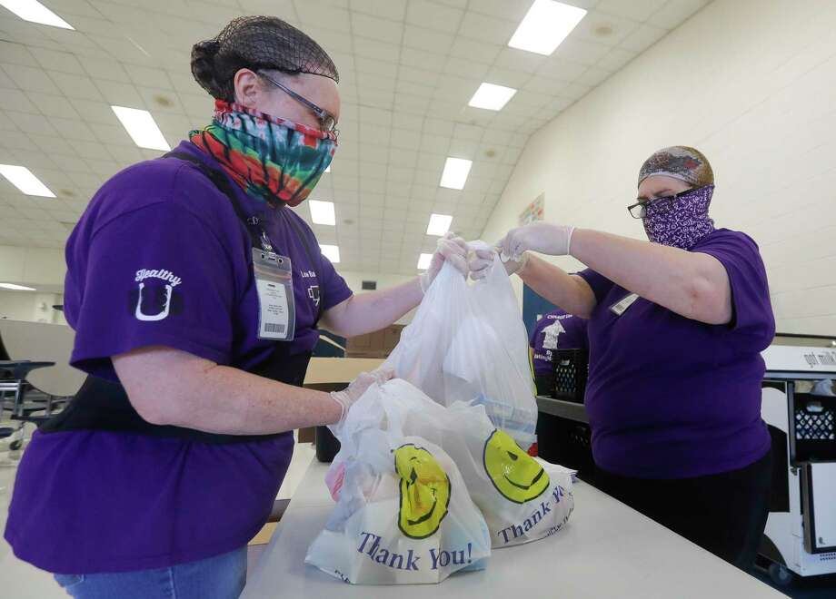 Angela Myers, right, hands Vicky Bugbee meals as 30 members of the New Caney ISD child nutrition department distributed 700 meals to students at New Caney Elementary School Aug. 26 in New Caney. The school was one of four distribution sites handing out meals for Thursday and Friday ahead of Hurricane Laura, a Category 4 storm, projected to make landfall Wednesday evening along the Texas-Louisiana border. Local school districts are looking forward to a boost in COVID-19 related funding from Montgomery County. Photo: Jason Fochtman, Houston Chronicle / Staff Photographer / 2020 © Houston Chronicle