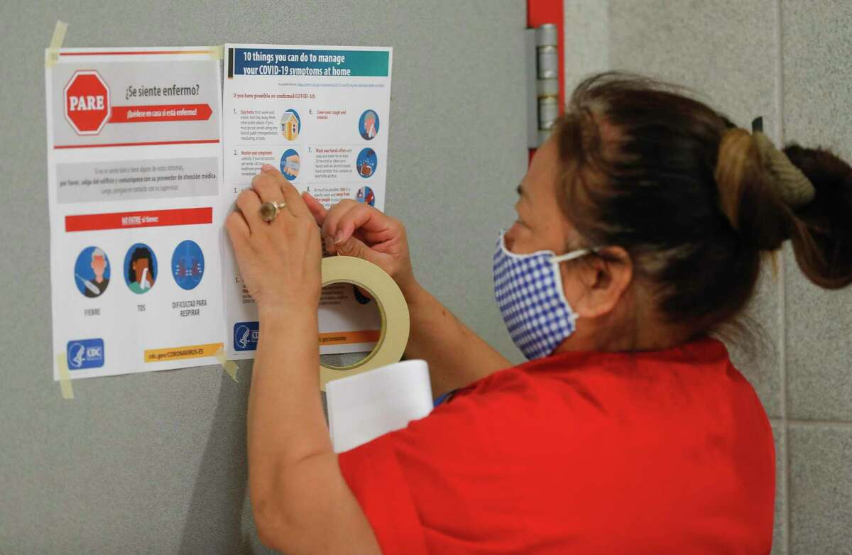 Splendora custodian Rosario Flores hangs coronavirus safety and sanitization signs on bathroom doors at Splendora High School Aug. 11 in Splendora. Local school districts are looking forward to a boost in COVID-19 related funding from Montgomery County.