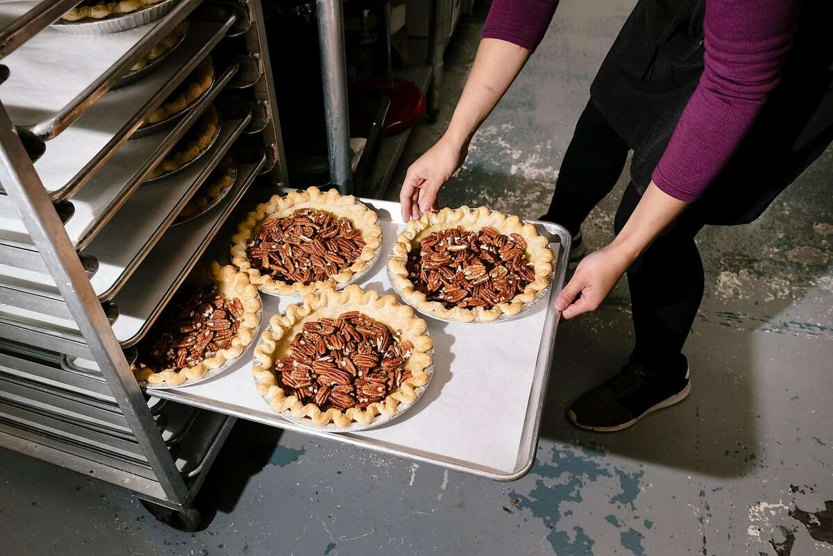 Julie Tran places Bourbon Pecan pies on a rack to cool while working at Three Babes Bakeshop.