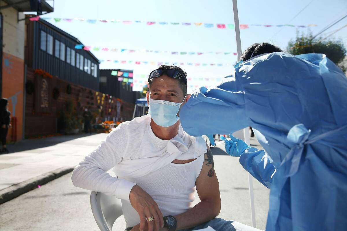 Department of Public Health registered nurse Po Lin Lui gives a flu shot to Jose Rodriguez at the Latino Task Force Resource Hub in San Francisco.