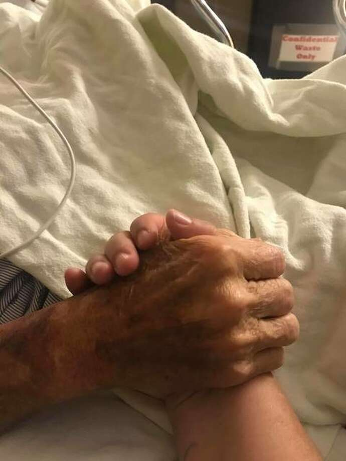 Sara Berkbigler holds her father's hand to comfort him before his death.