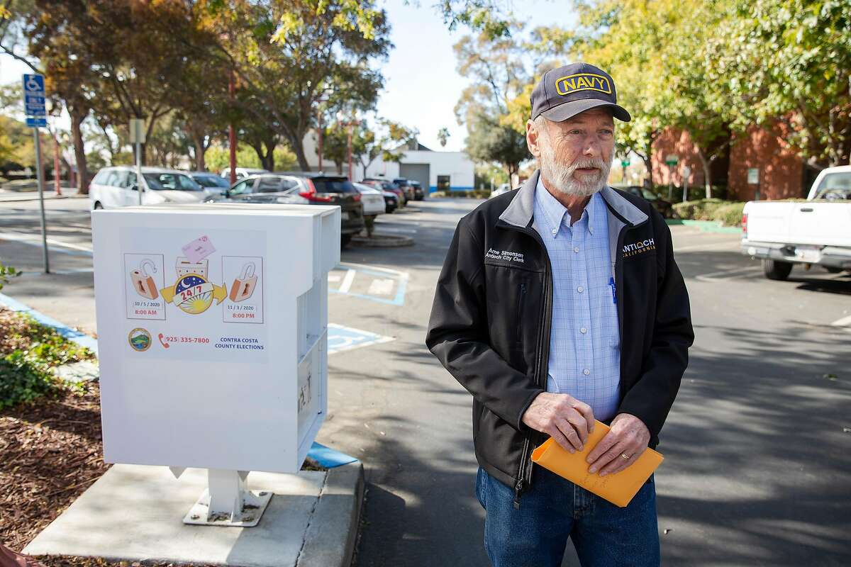 Arne Simonsen stands next to a voting boxing in front of City Hall in Antioch, Calif. on Friday, Nov. 6, 2020. Simonsen is a Trump supporter and the current Antioch City Clerk.