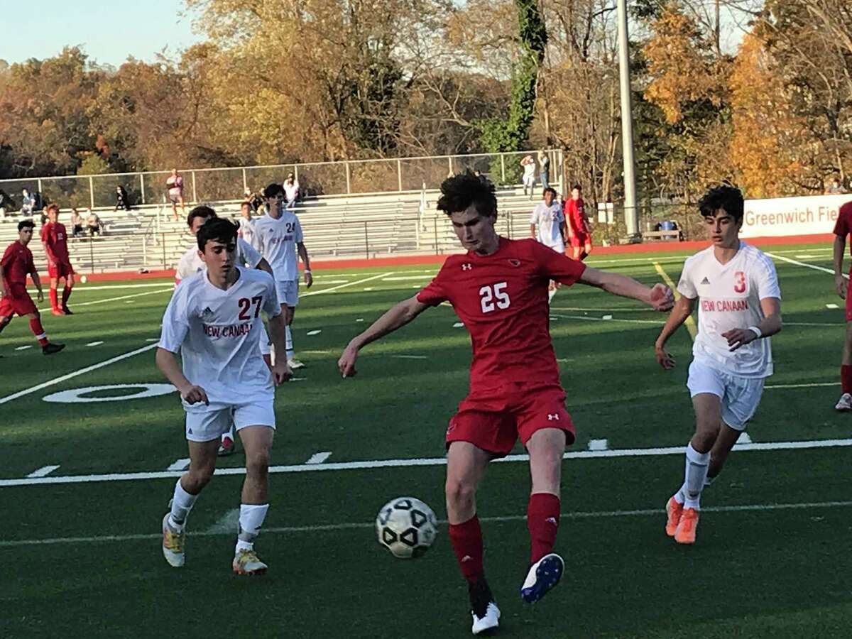 William Flynn of Greenwich, center, looks to get a touch on the ball during a boys soccer game between the Cardinals and New Canaan in the semifinals of the FCIAC West Region Tournament on Friday, Nov. 6, 2020, in Greenwich, Connecticut. Surrounding Flynn are New Canaan's Milan Afshar, left and Colin Mennitt.