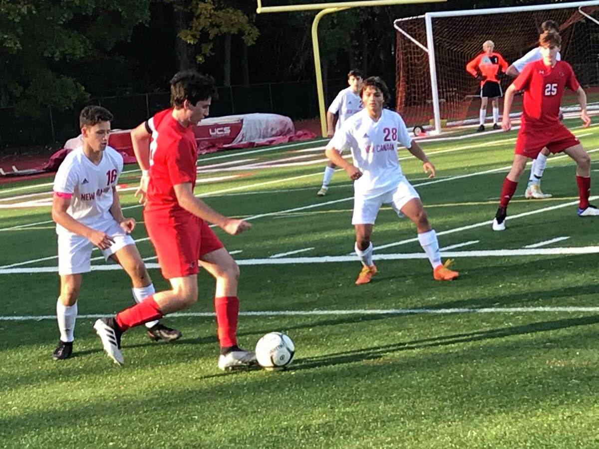 Matias Lew of Greenwich looks to pass the ball during a boys soccer game between the Cardinals and New Canaan in the semifinals of the FCIAC West Region Tournament on Friday, Nov. 6, 2020, in Greenwich, Connecticut. Closing in on Lew are New Canaan's Henry Lindberg, left, and Thomas Bausman. Greenwich posted a 2-0 win.