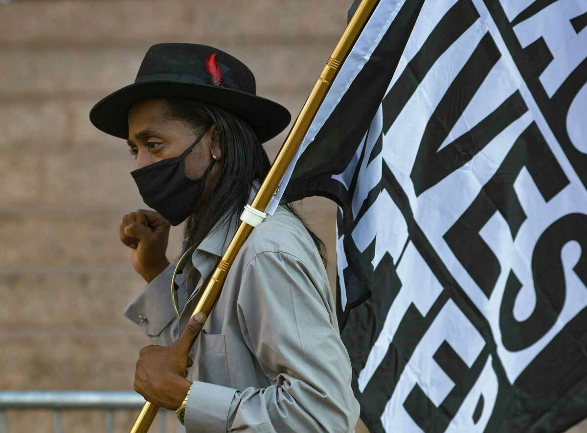 Pharaoh Clark carries a flag during an Ambitious Young Activists rally in downtown San Antonio on Friday, Sept. 25, 2020. The rally was held because a grand jury in Kentucky this week did not indict police officers who shot and killed Breonna Taylor, a Black woman, six times in March.