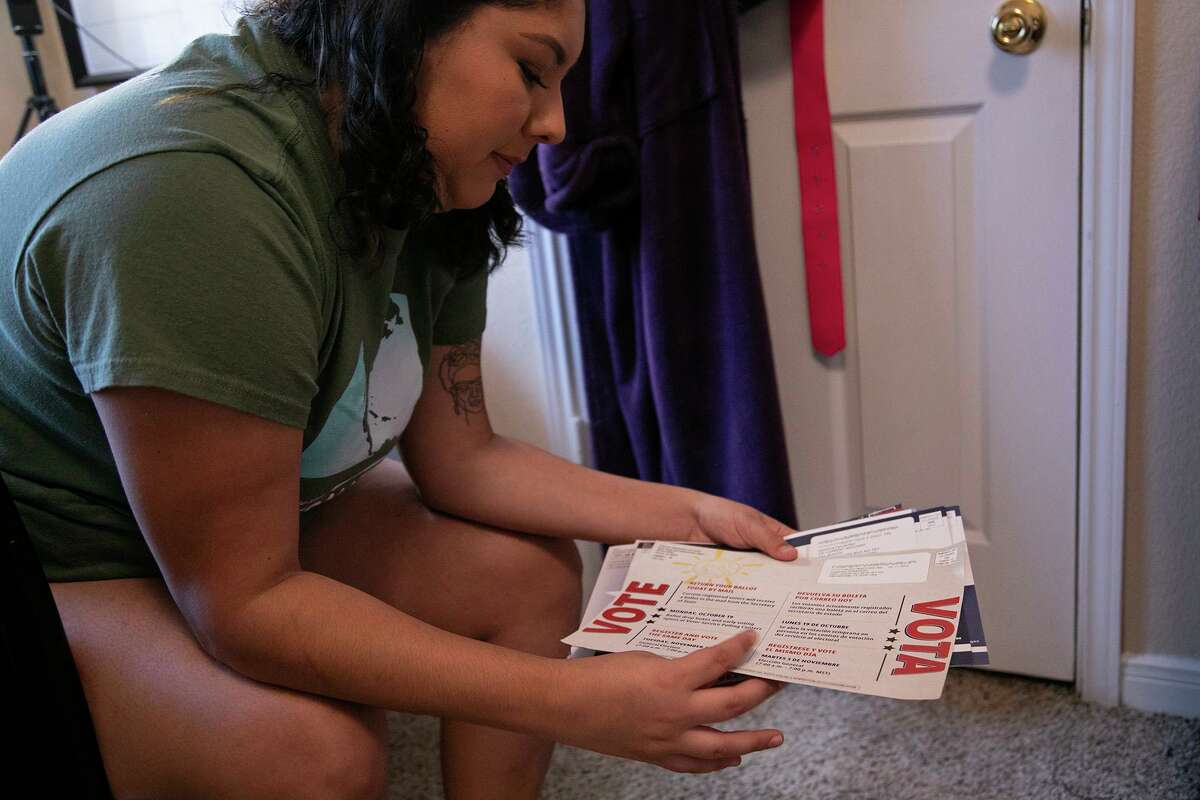 UTSA senior Josefina Fernandez holds campaign flyers she was involved with creating during a job earlier this year with the Democratic Congressional Campaign Committee.