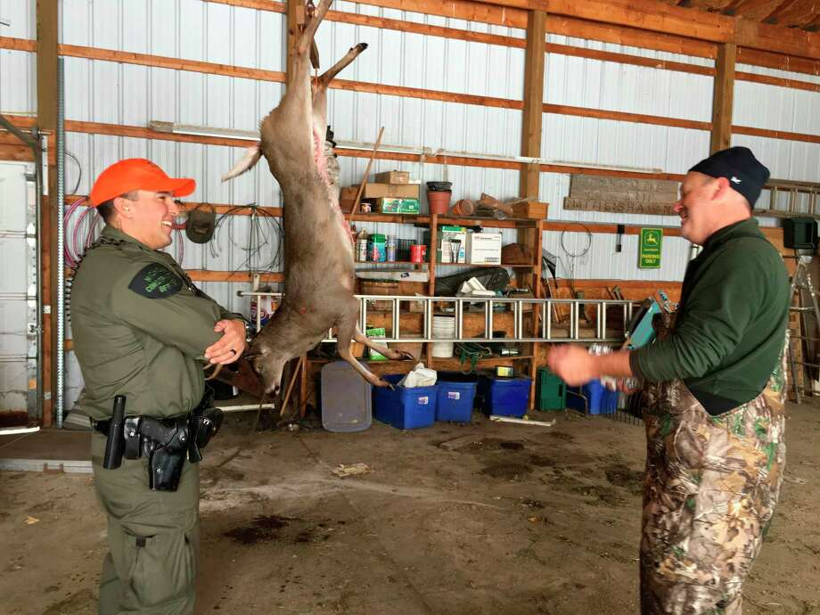 Conservation Officer Richard Cardenas listens to a successful hunter explain how he legally took his deer on opening day of the 2019 firearm season in Barry County, Michigan. (Courtesy Photo)