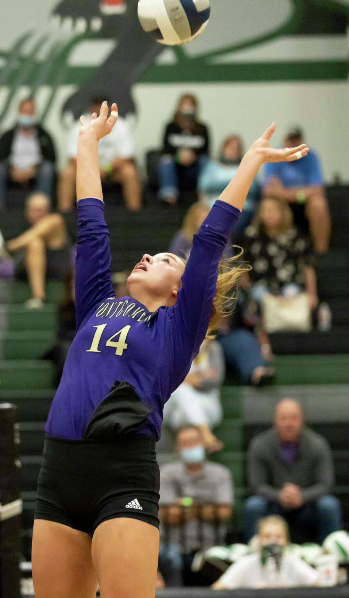 Montgomery setter Raina McWhirter (14) sets a play during the first set of a District 20-5A volleyball match at Kingwood Park High School in Kingwood.