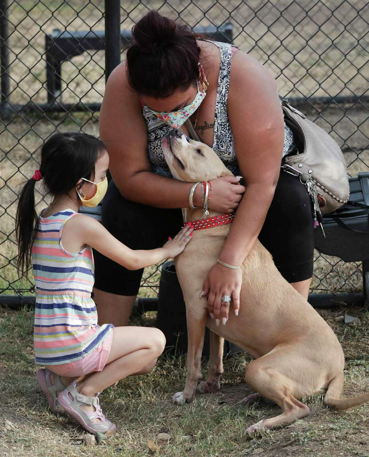 Perla Castellanos, center and her daughter Jocelyn Castellanos, 4, love on a dog they are thinking about adopting at Animal Care Services, on Friday, Nov. 6, 2020. The family is replacing a dog that passed away recently.