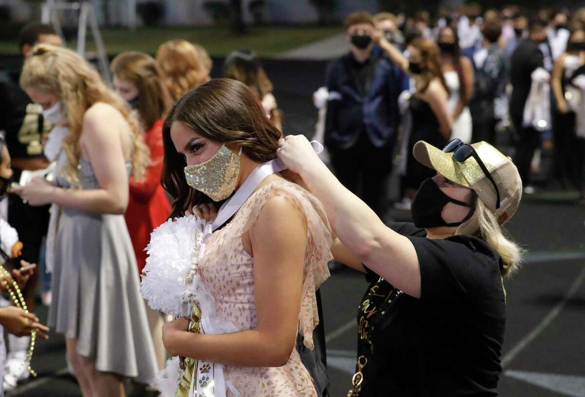 Hailey Britton, left, gets some help securing her homecoming mum from Amy Causey before a District 13-6A high school football game at Buddy Moorhead Stadium, Friday, Nov. 6, 2020, in Conroe.
