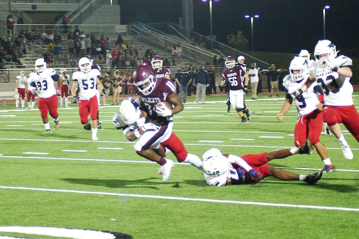 Clear Creek's Rocky Ketchum (34) fights to break the tackles of Clear Lake's Eric Hunter (4) and Clear Lake's Julian Humphrey (12)Friday, Nov. 6 at Challenger Columbia Stadium.