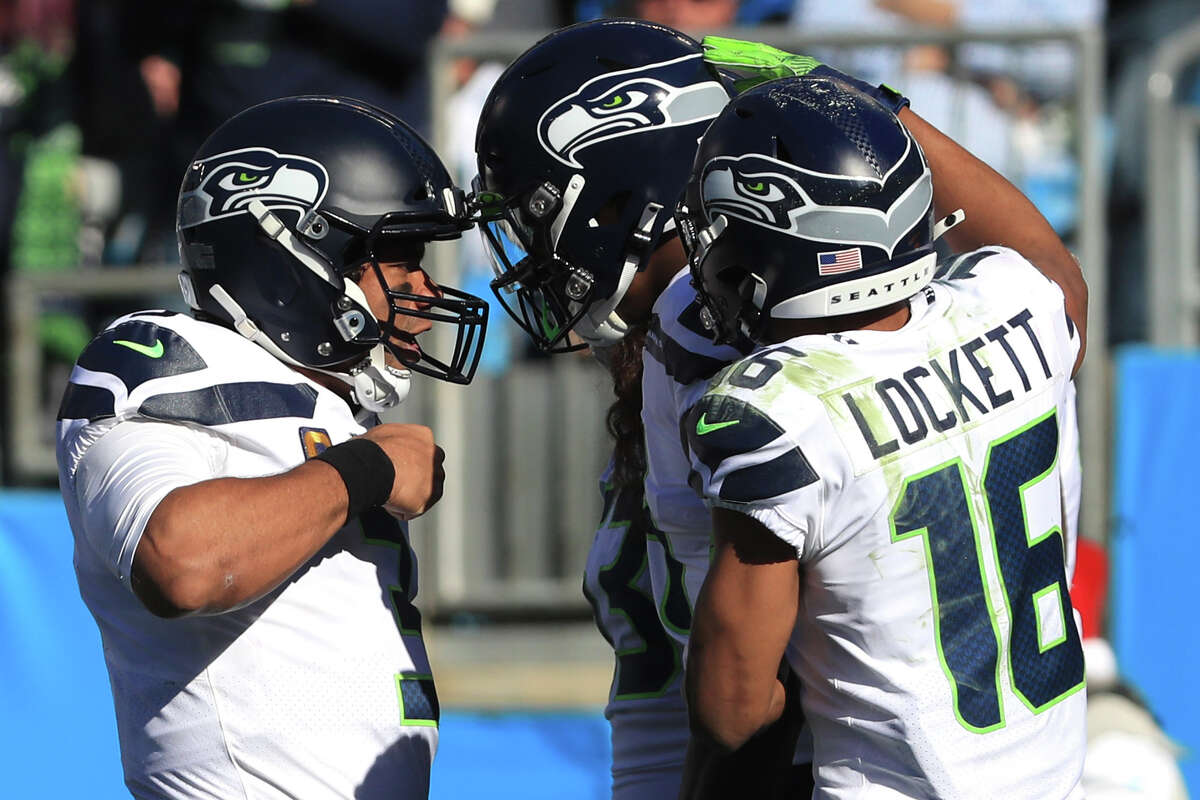 CHARLOTTE, NORTH CAROLINA - DECEMBER 15: Seattle Seahawks quarterback Russell Wilson #3, wide receiver Tyler Lockett #16 and wide receiver D.K. Metcalf #14 celebrate the touchdown in the first quarter against Carolina Panthers at Bank of America Stadium on December 15, 2019 in Charlotte, North Carolina. (Photo by Streeter Lecka/Getty Images)