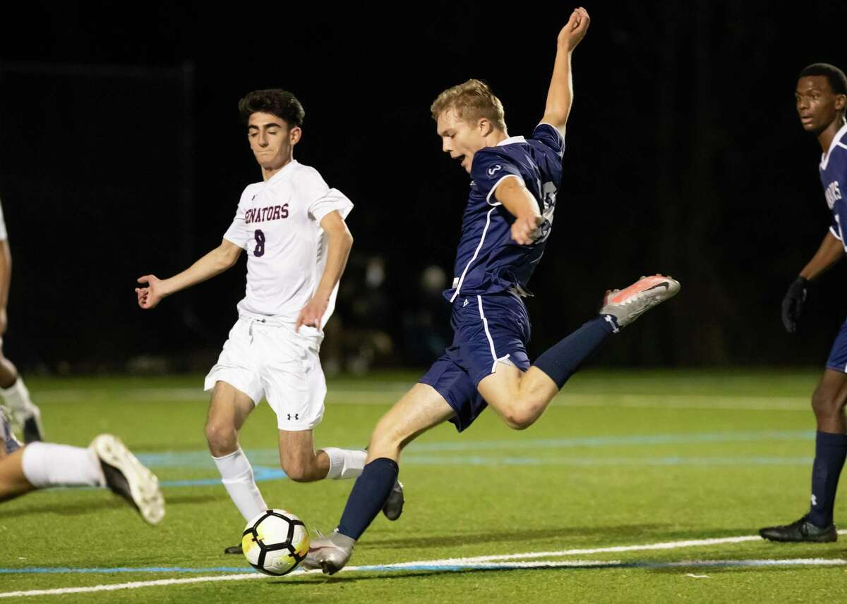 Wilton's Oliver Dahlen looks to take a shot while McMahon's Evangelos Mallios (8) defends in Friday night's FCIAC Central Region title game.