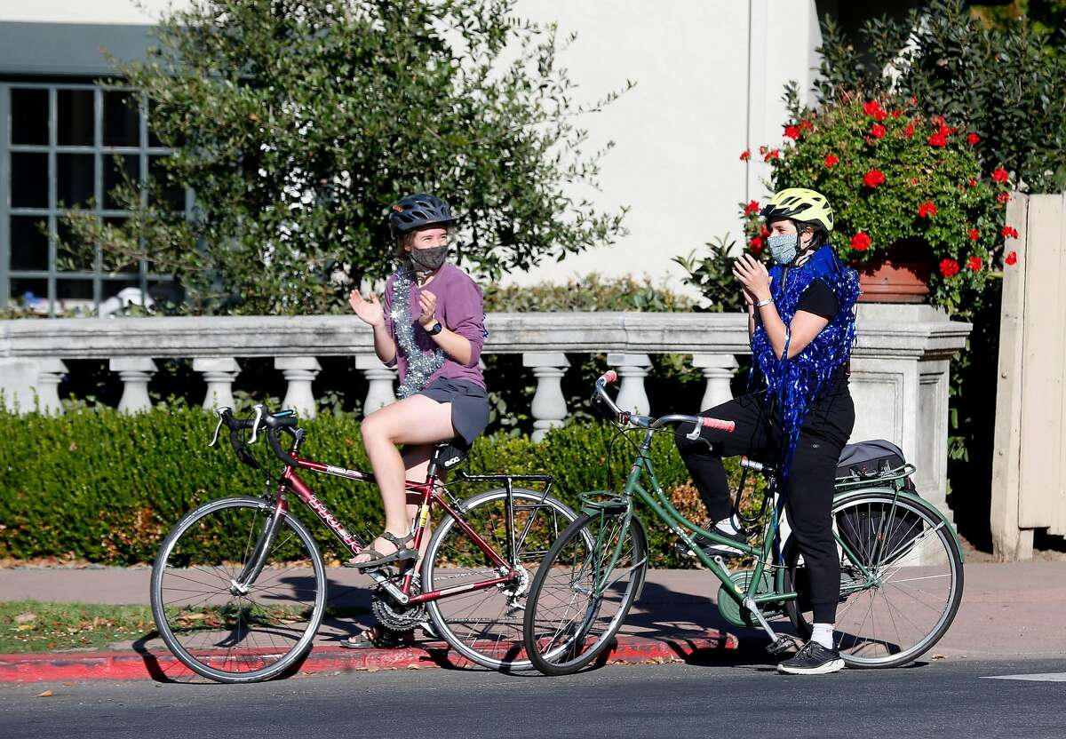 Bicyclists wear streamers as neighbors gather for a celebration on the fountain at the Marin Circle in Berkeley, Calif. on Saturday, Nov. 7, 2020 after Joe Biden is declared the winner over President Donald Trump in the presidential election.