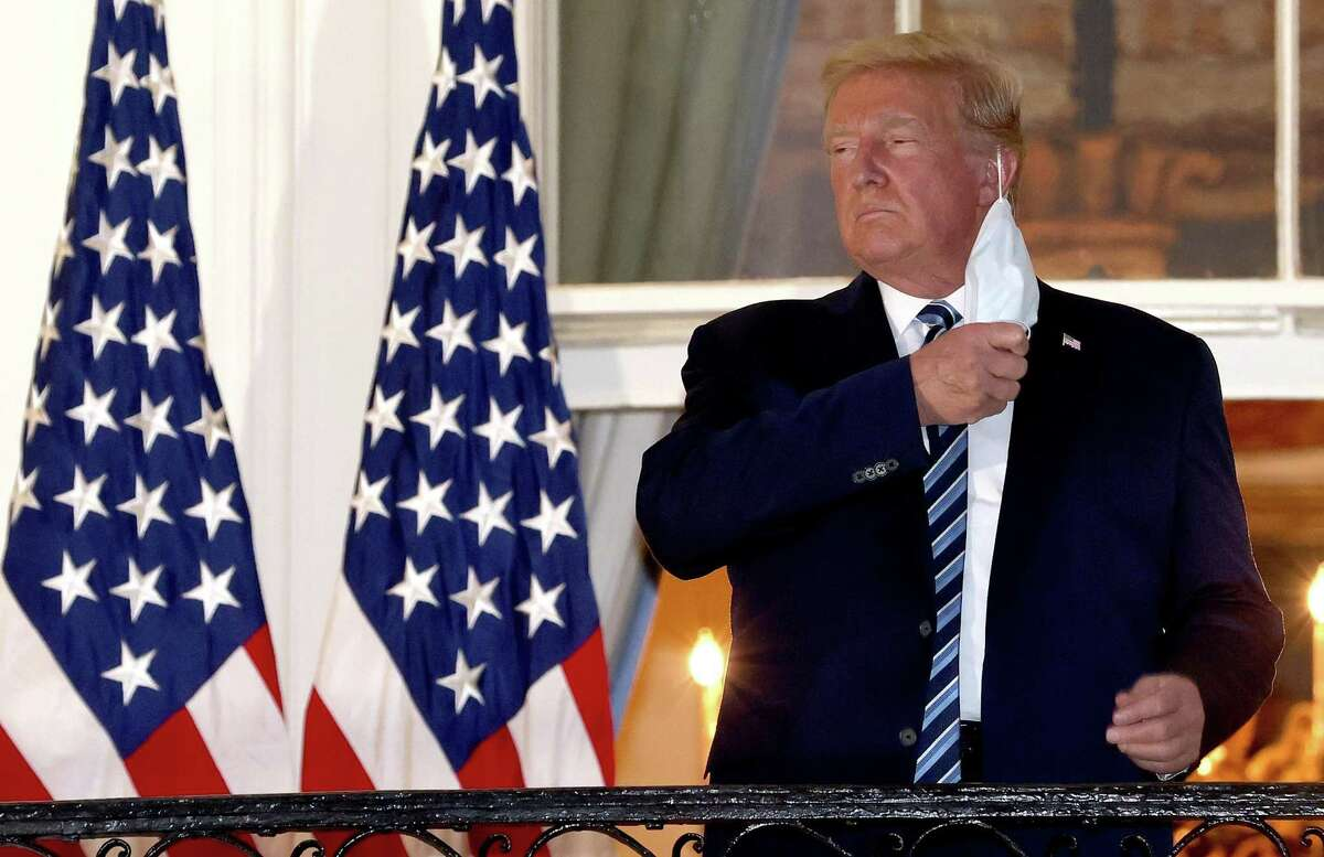 President Trump removes his mask upon his return to the White House from Walter Reed National Military Medical Center on Oct. 5. Trump spent three days hospitalized for COVID-19.