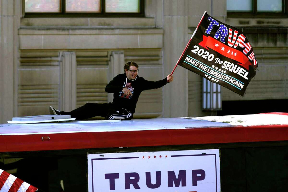A supporter of President Donald Trump waves a flag from atop a bus outside the Pennsylvania State Capitol, Saturday, Nov. 7, 2020, in Harrisburg, Pa., after Democrat Joe Biden defeated President Donald Trump to become 46th president of the United States.