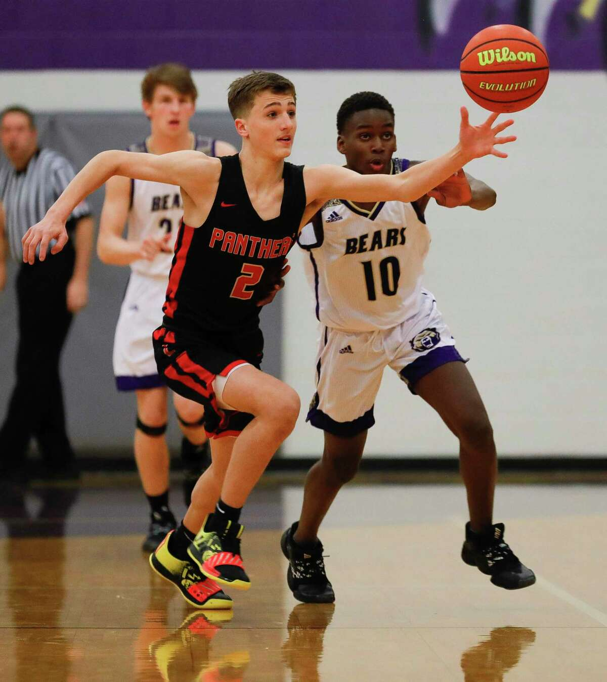 Montgomery point guard Hezzy Miregi (10) goes after a loose ball against Caney Creek shooting guard Kaleb Turner (2) during the first quarter of a District 20-5A high school basketball game at Montgomery High School, Tuesday, Jan. 7, 2020, in Montgomery.
