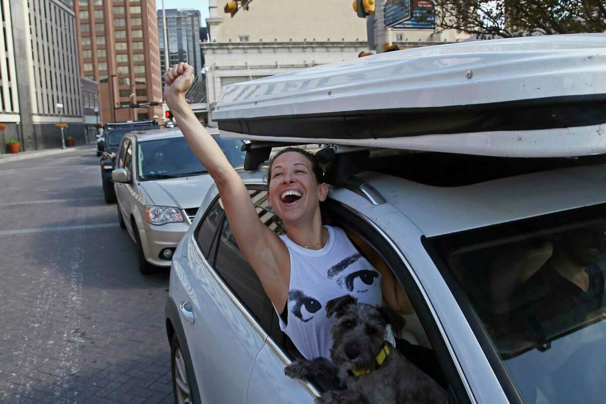 """Marissa Bennett celebrates as she joins in a Biden/Harris victory parade in downtown San Antonio, Saturday, Nov. 7, 2020. With her is """"Loki."""""""