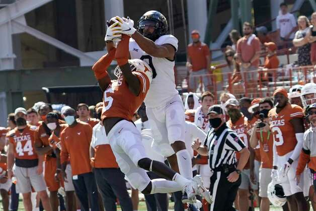 West Virginia's Isaiah Esdale (9) catches a pass over Texas' D'Shawn Jamison (5) during the first half of an NCAA college football game in Austin, Texas, Saturday, Nov. 7, 2020. (AP Photo/Chuck Burton) Photo: Chuck Burton, Associated Press / Copyright 2020 The Associated Press. All rights reserved.