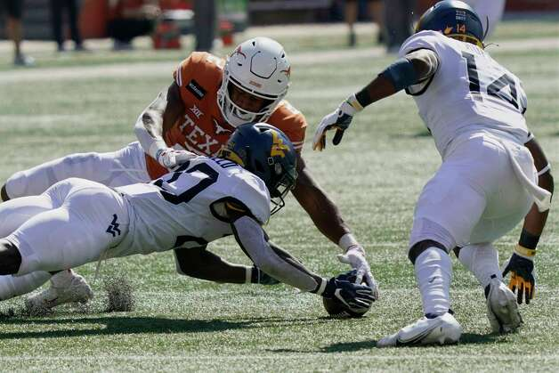 West Virginia's Alec Sinkfield (20) dives for a ball he fumbled against Texas' Roschon Johnson (2) during the first half of an NCAA college football game in Austin, Texas, Saturday, Nov. 7, 2020. West Virginia recovered the ball. (AP Photo/Chuck Burton) Photo: Chuck Burton, Associated Press / Copyright 2020 The Associated Press. All rights reserved.