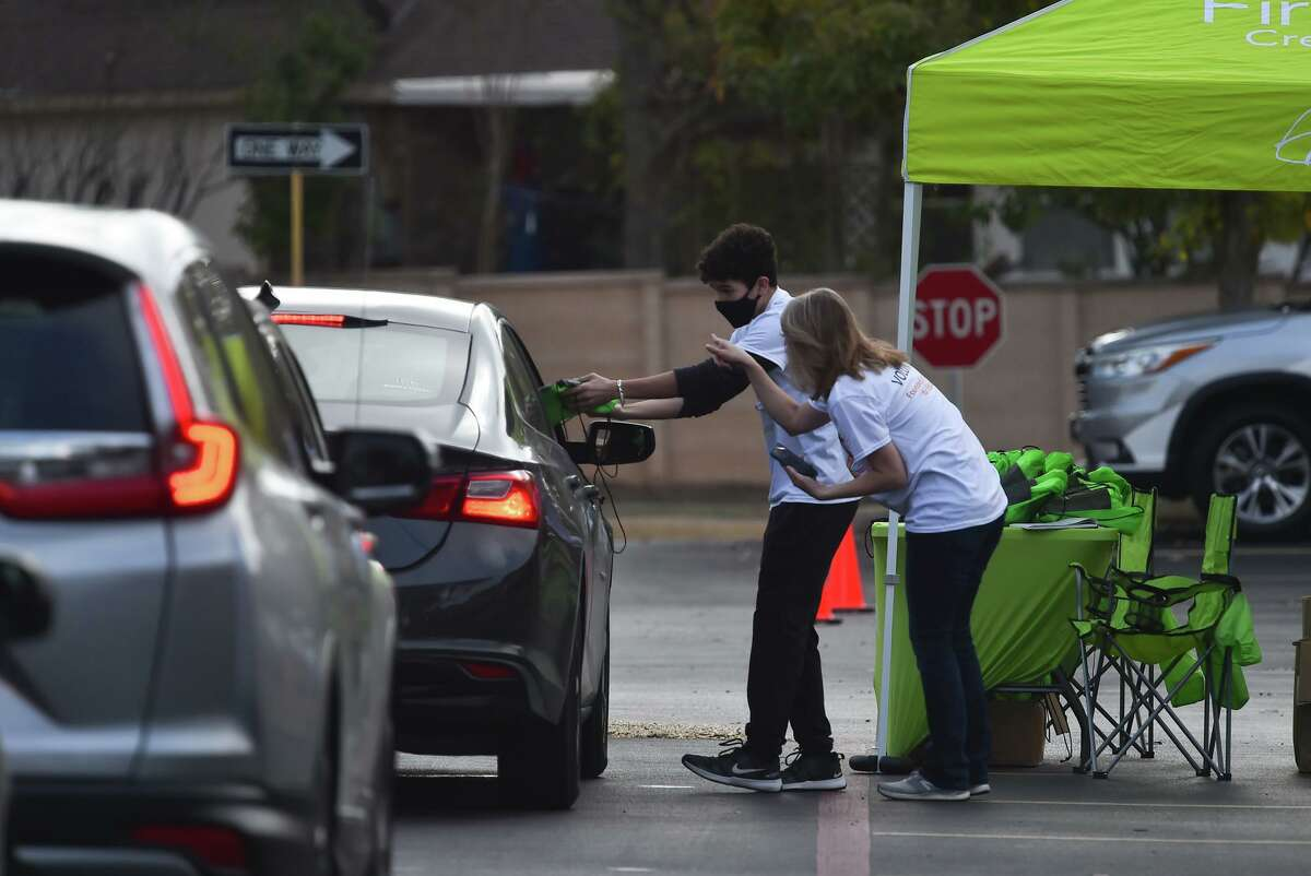 Noah Villa Franco and Christy Bradshaw hand out swag bags during Firstmark Credit Union's Turkeys for Teachers event, a drive-thru celebration in which volunteers also gave 1,000 free frozen turkeys to 1,000 teachers.