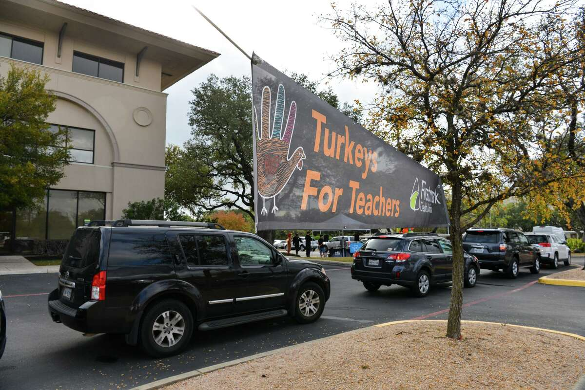 Cars line up as employee's and volunteers of Firstmark Credit Union hand out 1000 turkey's to 1000 teachers Saturday in the parking lot of their Gold Canyon Dr. location. Teachers were also given classroom supplies and swag bags filled with donated items from community members.