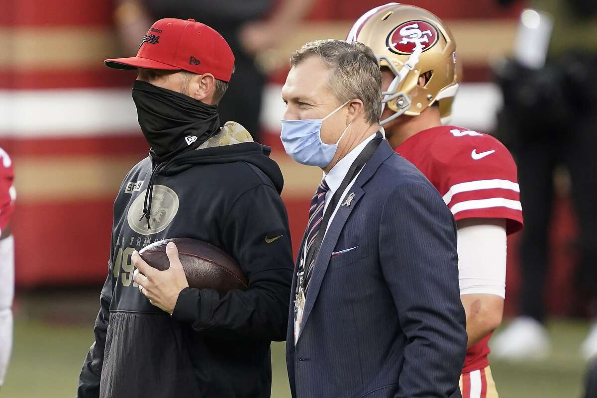 San Francisco 49ers head coach Kyle Shanahan, left, and general manager John Lynch watch players warm up before an NFL football game against the Green Bay Packers in Santa Clara, Calif., Thursday, Nov. 5, 2020. (AP Photo/Tony Avelar)