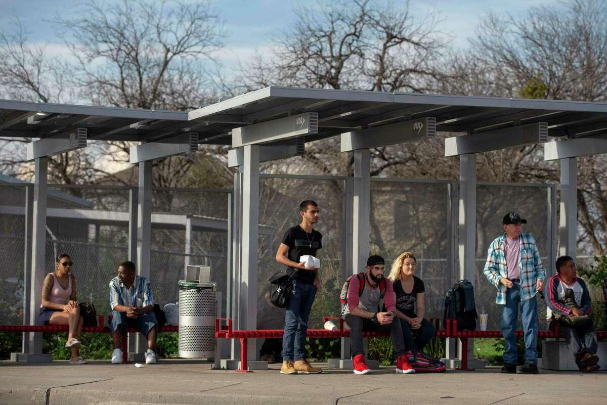 People wait for their bus at a VIA bus stop on East Fredericksburg Road in San Antonio, Texas, Feb. 4, 2020.