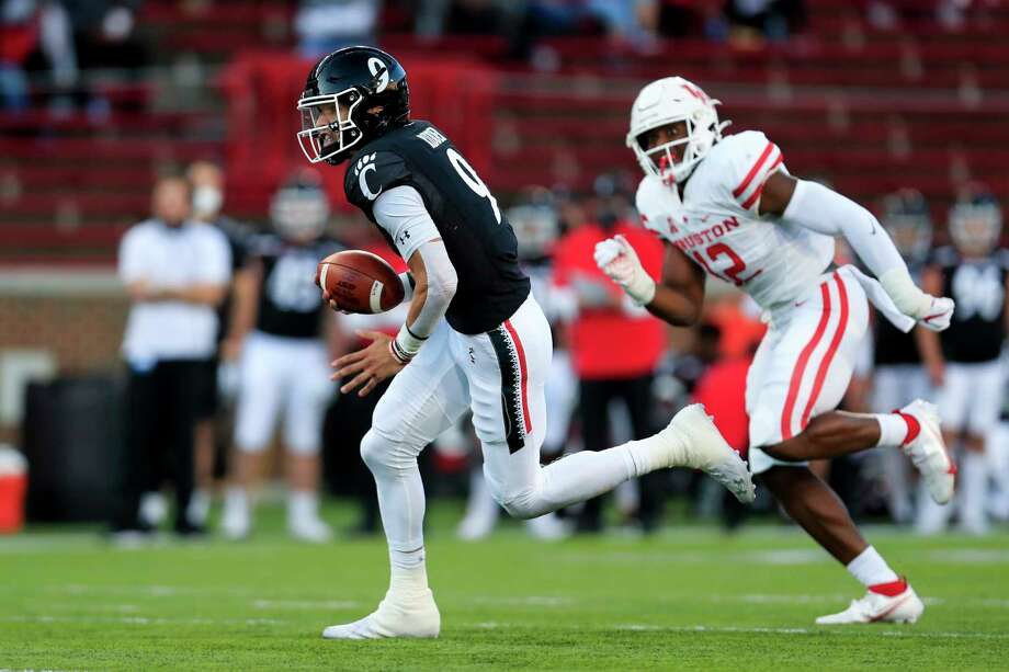 Cincinnati quarterback Desmond Ridder, left, carries the ball for a touchdown during the first half of an NCAA college football game against Houston, Saturday, Nov. 7, 2020, in Cincinnati. (AP Photo/Aaron Doster) Photo: Aaron Doster, Associated Press / Copyright 2020 The Associated Press. All rights reserved.