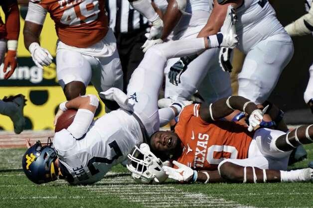 Texas' DeMarvion Overshown (0) loses his helmet as he sacks West Virginia quarterback Jarret Doege (2) during the second half of an NCAA college football game in Austin, Texas, Saturday, Nov. 7, 2020. (AP Photo/Chuck Burton) Photo: Chuck Burton, Associated Press / Copyright 2020 The Associated Press. All rights reserved.