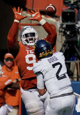 Texas' T'Vondre Sweat (93) blocks a pass by West Virginia's Jarret Doege (2) during the second half of an NCAA college football game in Austin, Texas, Saturday, Nov. 7, 2020. (AP Photo/Chuck Burton) Photo: Chuck Burton, Associated Press / Copyright 2020 The Associated Press. All rights reserved.