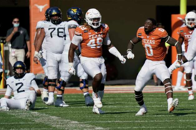 Texas' DeMarvion Overshown (0) celebrates with teammates Ta'Quon Graham (49) after his sack of West Virginia quarterback Jarret Doege (2) during the second half of an NCAA college football game in Austin, Texas, Saturday, Nov. 7, 2020. (AP Photo/Chuck Burton) Photo: Chuck Burton, Associated Press / Copyright 2020 The Associated Press. All rights reserved.