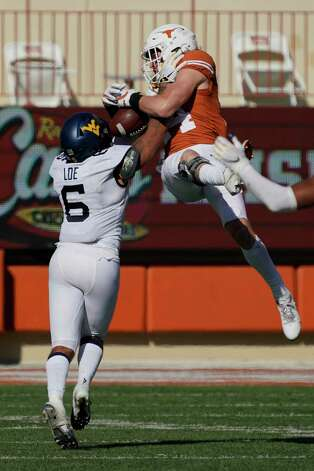 Texas' Brenden Schooler (14) tries to catch a pass as West Virginia's Dreshun Miller (5) defends during the second half of an NCAA college football game in Austin, Texas, Saturday, Nov. 7, 2020. The pass was incomplete. (AP Photo/Chuck Burton) Photo: Chuck Burton, Associated Press / Copyright 2020 The Associated Press. All rights reserved.