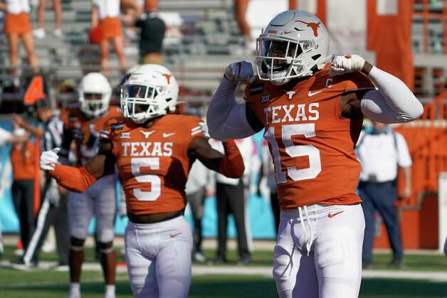 Texas' Chris Brown (15) and D'Shawn Jamison (5) celebrates after a stop against West Virginia on fourth down late during the second half of an NCAA college football game in Austin, Texas, Saturday, Nov. 7, 2020. (AP Photo/Chuck Burton) Photo: Chuck Burton, Associated Press / Copyright 2020 The Associated Press. All rights reserved.