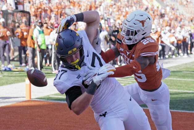 Texas' B.J. Foster (25) knocks the ball away from West Virginia's Mike O'Laughlin (87) during the second half of an NCAA college football game in Austin, Texas, Saturday, Nov. 7, 2020. (AP Photo/Chuck Burton) Photo: Chuck Burton, Associated Press / Copyright 2020 The Associated Press. All rights reserved.