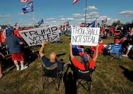 """Trump supporters hold up signs as Congressmen Kevin Brady, R-The Woodlands, addresses a crowd of several hundred people during a """"Defend Our President"""" rally at the Montgomery County Fairgrounds, Saturday, Nov. 7, 2020, in Conroe."""