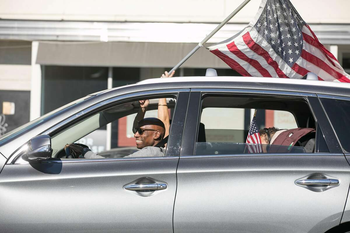 A carload of people wave American flags celebrating Democratic Presidential candidate Joe Biden�s victory over President Donald Trump in Oakland, California on Nov. 7, 2020.