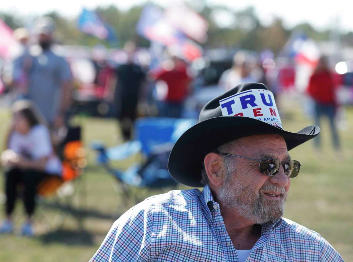 """Ellis Moses wearsa a cowboy hat with a Trump Pence sign during a """"Defend Our President"""" rally at the Montgomery County Fairgrounds, Saturday, Nov. 7, 2020, in Conroe."""