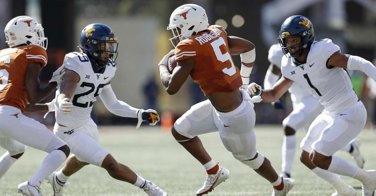 Bijan Robinson #5 of the Texas Longhorns carries the ball defended by Tony Fields II #1 of the West Virginia Mountaineers and Sean Mahone #29 int he first quarter at Darrell K Royal-Texas Memorial Stadium on November 07, 2020 in Austin, Texas. (Photo by Tim Warner/Getty Images)