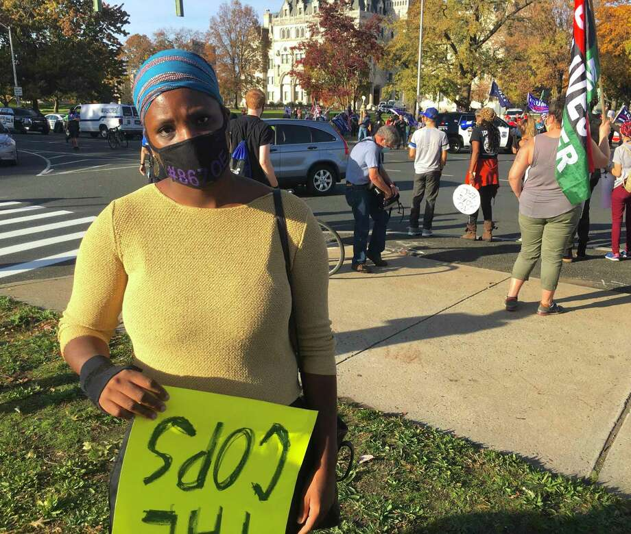 Tenaya Taylor, a Hartford activist for racial equity, attended a social justice rally in Hartford after Joe Biden was declared president-elect. She carried a sign opposing police, drawing the ire of Trump supporters who held a rally in the same place. Photo: Dan Haar / Hearst Connecticut Media
