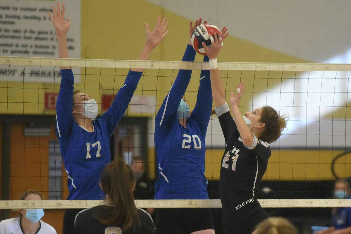 Trumbull's Ali Castro battles Ludlowe's Tatum Holderied (17) and Caitlin Finnegan (20) at the net during the FCIAC East Region girls volleyball final in Trumbull on Saturday.