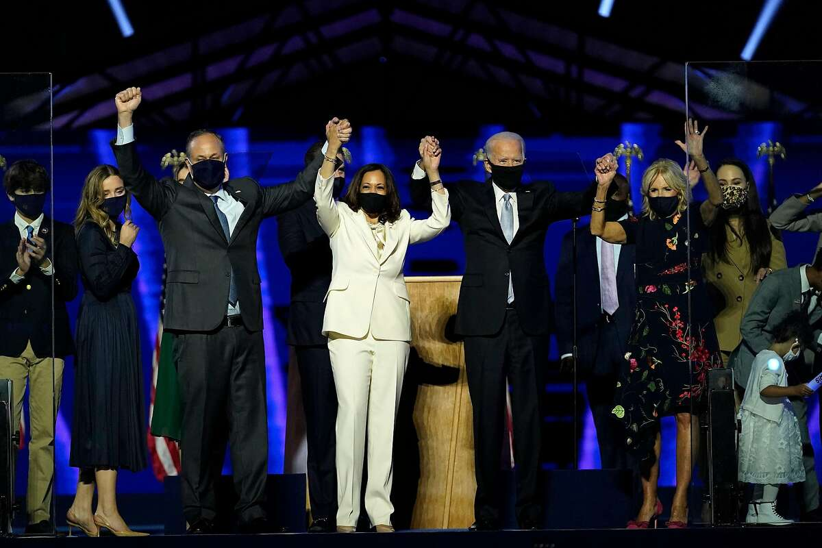 (From L) Husband of Vice President-elect Kamala Harris, Douglas Emhoff, Vice President-elect Kamala Harris, US President-elect Joe Biden and wife Jill Biden salute the crowd after delivering remarks in Wilmington, Delaware, on November 7, 2020, after being declared the winners of the presidential election.