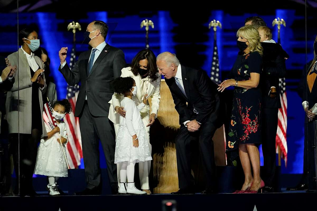 US Vice President-elect Kamala Harris and US President-elect Joe Biden stand on stage with family in Wilmington, Delaware, on November 7, 2020, after being declared the winner of the presidential election.