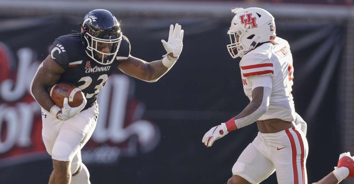 Gerrid Doaks #23 of the Cincinnati Bearcats tries to fend off the approaching tackle from JoVanni Stewart #9 of the Houston Cougars during the first half at Nippert Stadium on November 7, 2020 in Cincinnati, Ohio. (Photo by Michael Hickey/Getty Images)